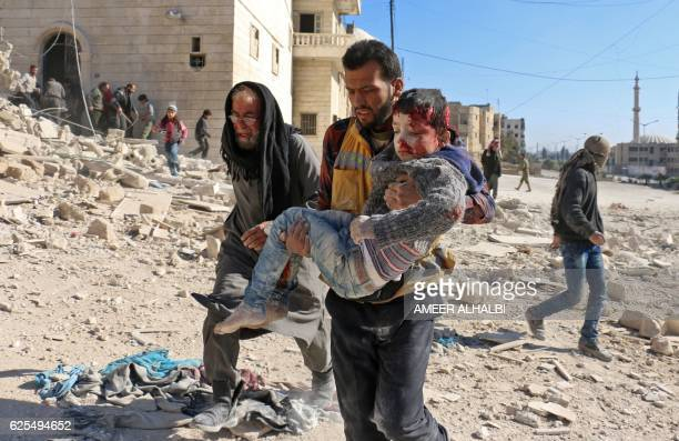 A Syrian civil defence volunteer known as the White Helmets carries a boy rescued from the rubble following a reported barrel bomb attack on the Bab...