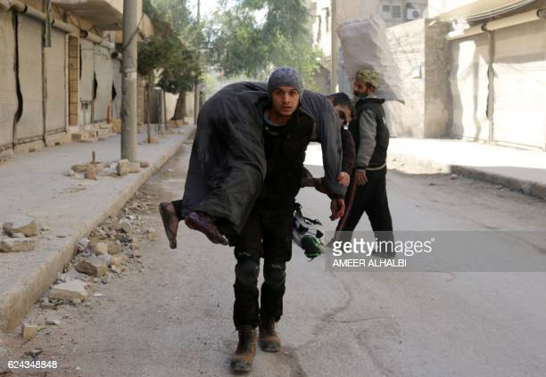 A Syrian civil defence volunteer known as the White Helmets carries an injured man on November 19 2016 following a reported air strike on Aleppo's...