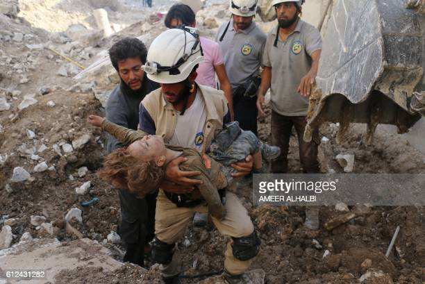 Syrian civil defence volunteer known as the White Helmets holds the body of a child after he was pulled from the rubble following a government forces...