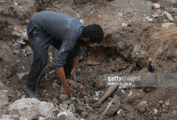 Syrian civil defence volunteer removes the rubble from around the body of a victim following a government forces air strike on the rebelheld...