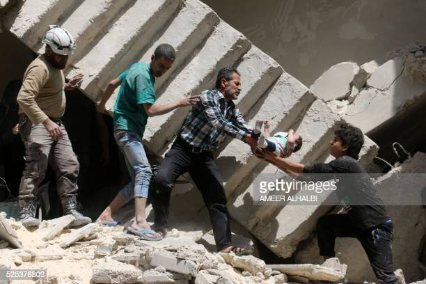 TOPSHOT Syrian civil defence volunteers and rescuers remove a baby from under the rubble of a destroyed building following a reported air strike on...