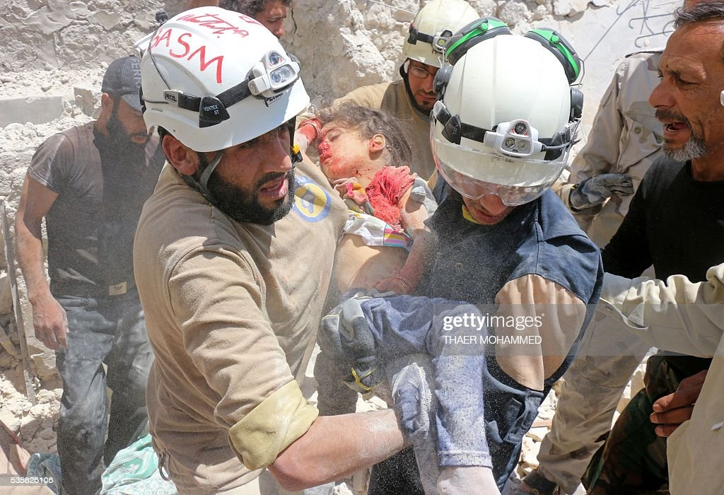Syrian civil defence volunteers carry the body of a girl, dug out from the rubble, following a reported attack by Syrian government forces on the Sakhour eastern neighbourhood, in the northern Syrian city of Aleppo, on May 30, 2016. / AFP / Thaer Mohammed