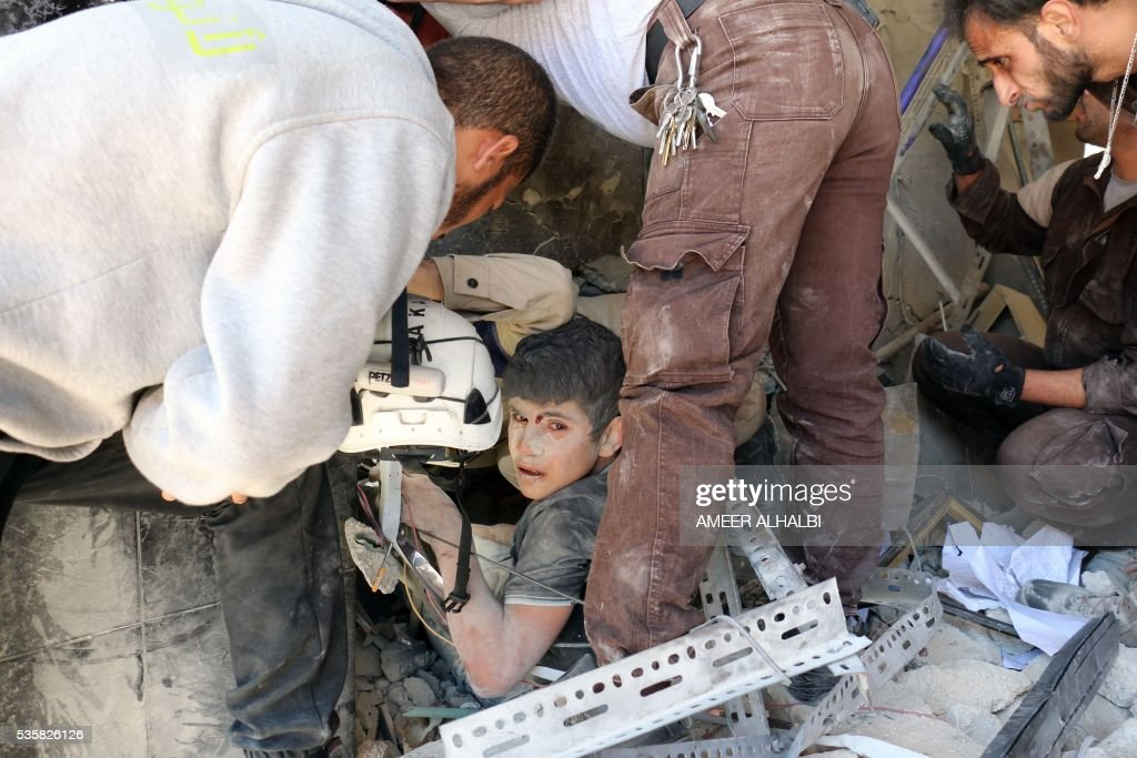 Syrian civil defence volunteers help a boy out of the rubble following a reported attack by Syrian government forces on May 30, 2016, in the Tariq al-Bab neighbourhood in the northern city of Aleppo. / AFP / AMEER