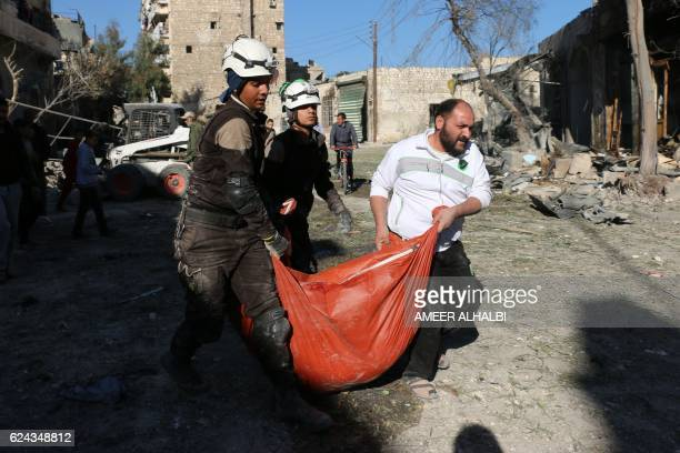 Syrian civil defence volunteers known as the White Helmets carry a tarpaulin on November 19 2016 following a reported air strike on Aleppo's...