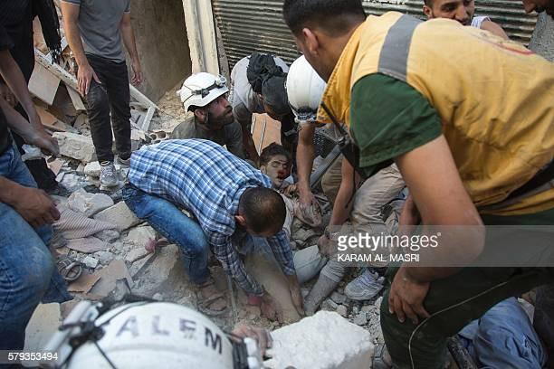 TOPSHOT Syrian civil defence volunteers known as the White Helmets dig a body out from the rubble of a building following a reported airstrike on the...