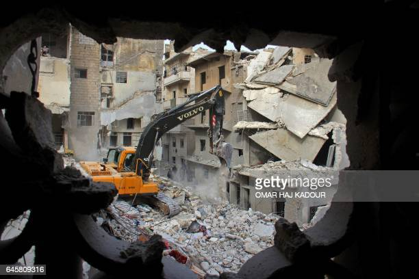 TOPSHOT Syrian civil defence volunteers known as the White Helmets look for survivors amidst the debris following reported government airstrike on...
