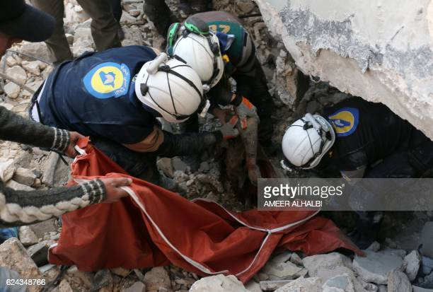 Syrian civil defence volunteers known as the White Helmets pull a body from the rubble of a destroyed building on November 19 2016 following a...