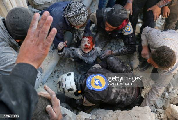 TOPSHOT Syrian civil defence volunteers known as the White Helmets rescue a boy from the rubble following a reported barrel bomb attack on the Bab...