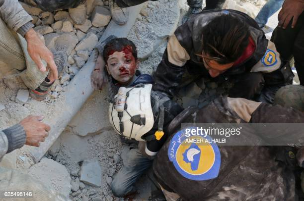 Syrian civil defence volunteers known as the White Helmets rescue a boy from the rubble following a reported barrel bomb attack on the Bab alNairab...