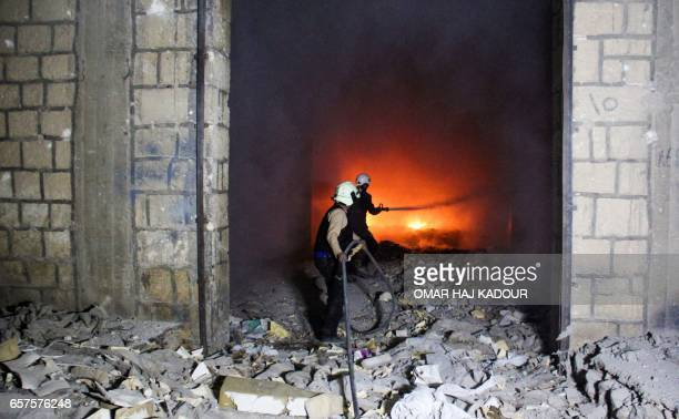 TOPSHOT Syrian civil defence volunteers known as the White Helmets try to extinguish fire reportedly caused by air strikes in the northwestern city...