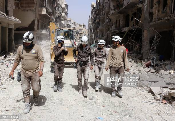 Syrian civil defence volunteers known as the White Helmets walk amidst the debris following a reported air strike by Syrian government forces in the...