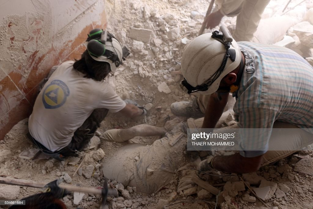 Syrian civil defence volunteers pull a body from under the rubble following a reported attack by Syrian government forces on May 27, 2016, in the Tariq al-Bab neighbourhood in the northern city of Aleppo. / AFP / THAER