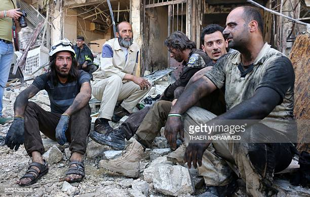 Syrian civil defence volunteers rest following a reported airstrike on April 23 2016 in the rebelheld neighbourhood of Tareeq alBab in the northern...