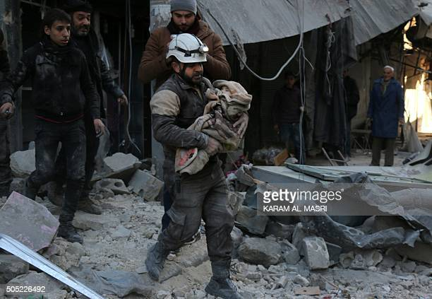 A Syrian Civil Defence worker carries a child wrapped in a blanket over the rubble following a reported air strike by Syrian government forces on the...