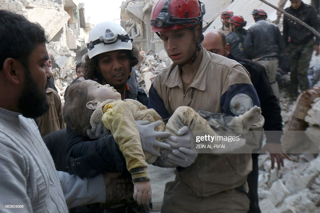 Syrian Civil Defence workers carry the body of a child on February 1 following a reported air strike by Syrian government forces in the northern city...