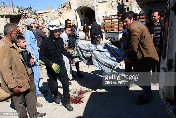 Syrian Civil Defence workers carry the body of one of several people killed in a reported barrel bomb attack by Syrian government forces on March 5...