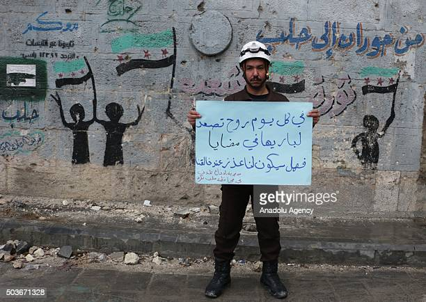 Syrian civil defense team members hold banners as they gather to protest for civilians who starved to death in Madaya on January 6 2016 in Aleppo...