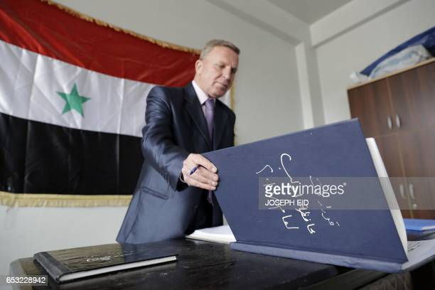 A Syrian civil servant at the Idlib governorate administration checks a register at his temporary quarters some 90 kilometres from the original...