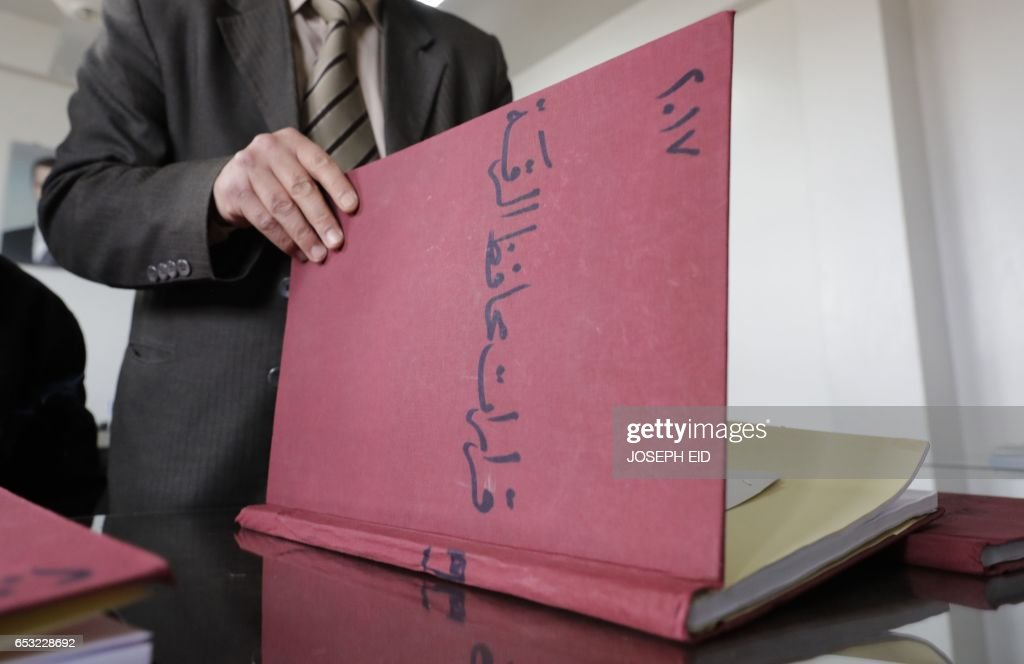 A Syrian civil servant at the Raqa governorate administration checks a register at his temporary quarters, some 220 kilometres (135 miles) from the original premises in Raqa, which was the first provincial capital to be lost by the government in March 2013, in a building provided by the Hama governorate administration in the city of Hama in central Syria on March 13, 2017. /