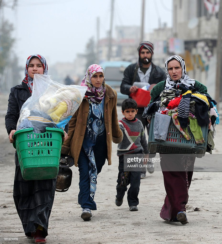 Syrian civilians carry their belongings as they flee the violence in the Sheikh Said district of the northern city of Aleppo on February 10, 2013. Syrian rebels launched fierce assaults on regime troops in several parts of the country, including near Deir Ezzor where they used tanks to shell an army brigade, a watchdog and activists said. AFP PHOTO/AAMIR QURESHI