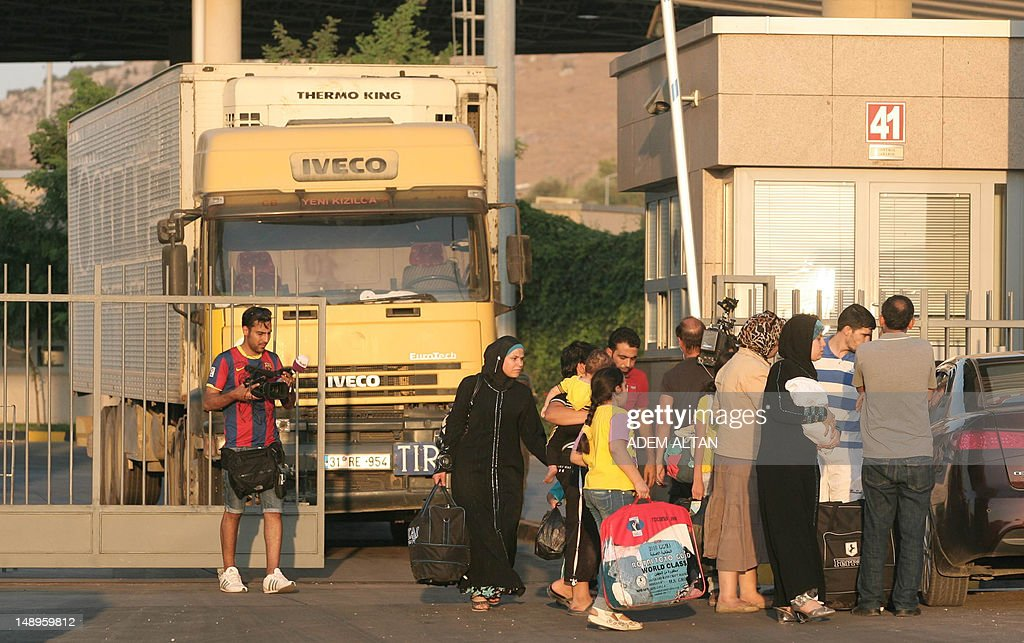 Syrian civilians cross from Syria into Turkey's border post at Cilvegozu in southern province of Hatay on July 20, 2012. An AFP photographer saw the burned shells of lorries scattered across the scene of Thursday's battle, and some 150 armed rebel fighters remained at the Syrian post, which lies opposite Turkey's Cilvegozu border crossing in the southern province of Hatay.