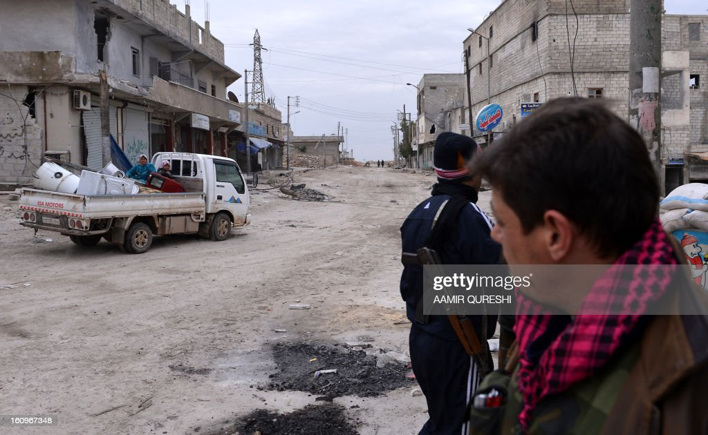 Syrian civilians drive past rebels as they flee violence in the Sheikh Said district of the northern city of Aleppo on February 8, 2013. Syrian forces shelled rebel belts, the Syrian Observatory for Human Rights said, as an army offensive raged into a third straight day.