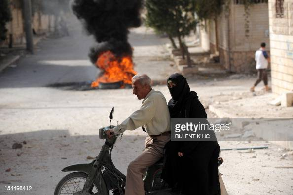 Syrian civilians ride a motorcycle past burning tyres set on fire by rebels in order for the black smoke to obscure the vision of regime pilots in...