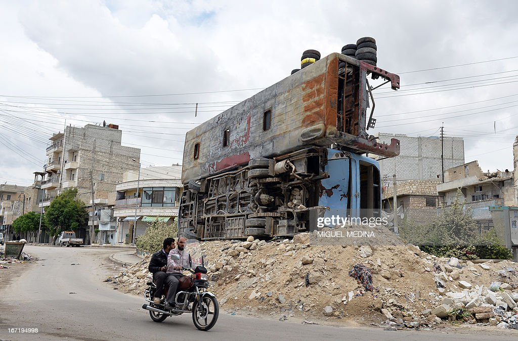 Syrian civilians ride past two destroyed buses piled up on rubble in the northern city of Aleppo on April 22, 2013. The European Union offered fresh aid to Syria's opposition, easing an EU oil embargo in favour of the rebels fighting President Bashar al-Assad, but stopping short of supplying offensive weapons.