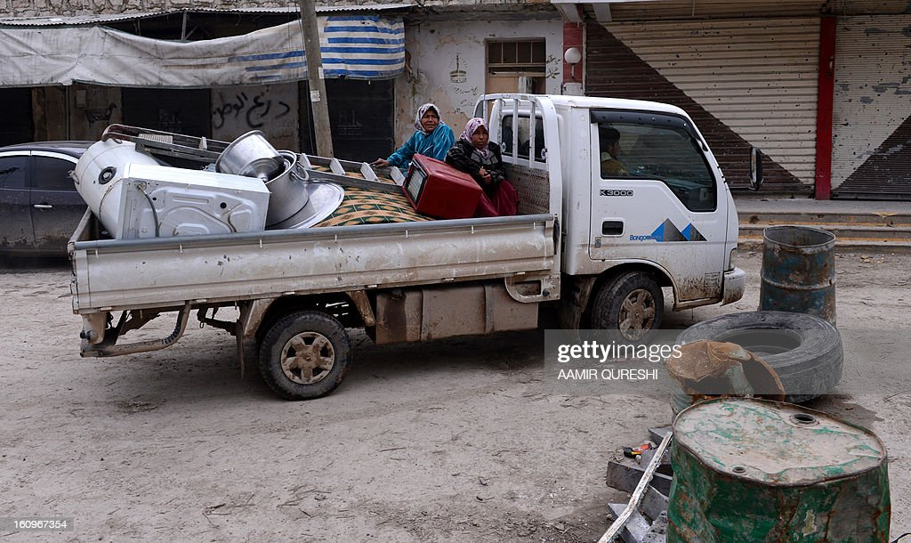 Syrian civilians sit in the back of a pick-up truck loaded with their belongings as they flee violence in the Sheikh Said district of the northern city of Aleppo on February 8, 2013. Syrian forces shelled rebel belts, the Syrian Observatory for Human Rights said, as an army offensive raged into a third straight day. AFP PHOTO/AAMIR QURESHI