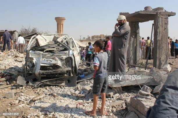 Syrian civilians stand at the site where a Syrian government forces aircraft fell after it was shot down by militants of the Islamic State group over...