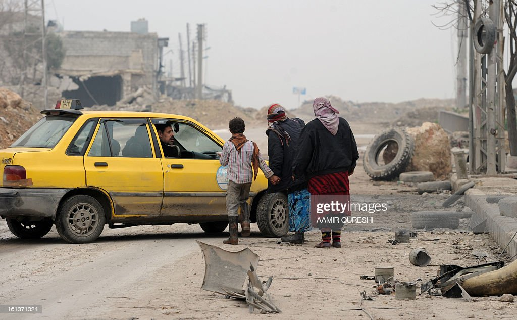 Syrian civilians talk with a taxi driver as they flee the violence in the Sheikh Said district of the northern city of Aleppo on February 10, 2013. Syrian rebels launched fierce assaults on regime troops in several parts of the country, including near Deir Ezzor where they used tanks to shell an army brigade, a watchdog and activists said. AFP PHOTO/AAMIR QURESHI