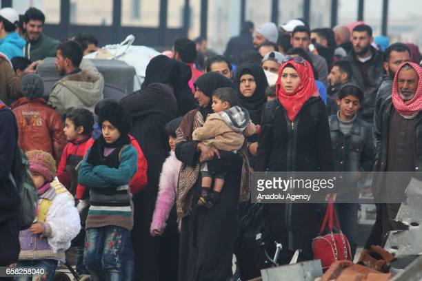 Syrian civilians wait for buses to be evacuated from AlWaer district of Homs in Aleppo Syria on March 27 2017 Second group of around 1800 people to...