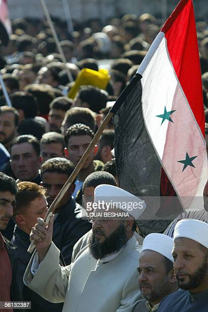 Syrian clergyman waves his national flag among demonstrators who gathered at Damascus University as President Bashar alAssad was delivering a speech...
