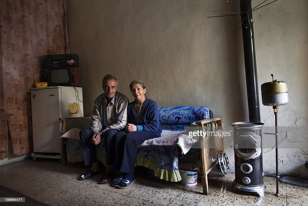 Syrian couple Michael Oberi, 53, and Sarbi Magarian, 51, sit in their room of the St Elie Rest Home, founded in 1863, in Aleppo on January 02, 2013. The aging Christians holed up inside the retirement home in the devastated northern Syrian city of Aleppo have no light, no telephone lines, and little idea of what is happening in the outside world.