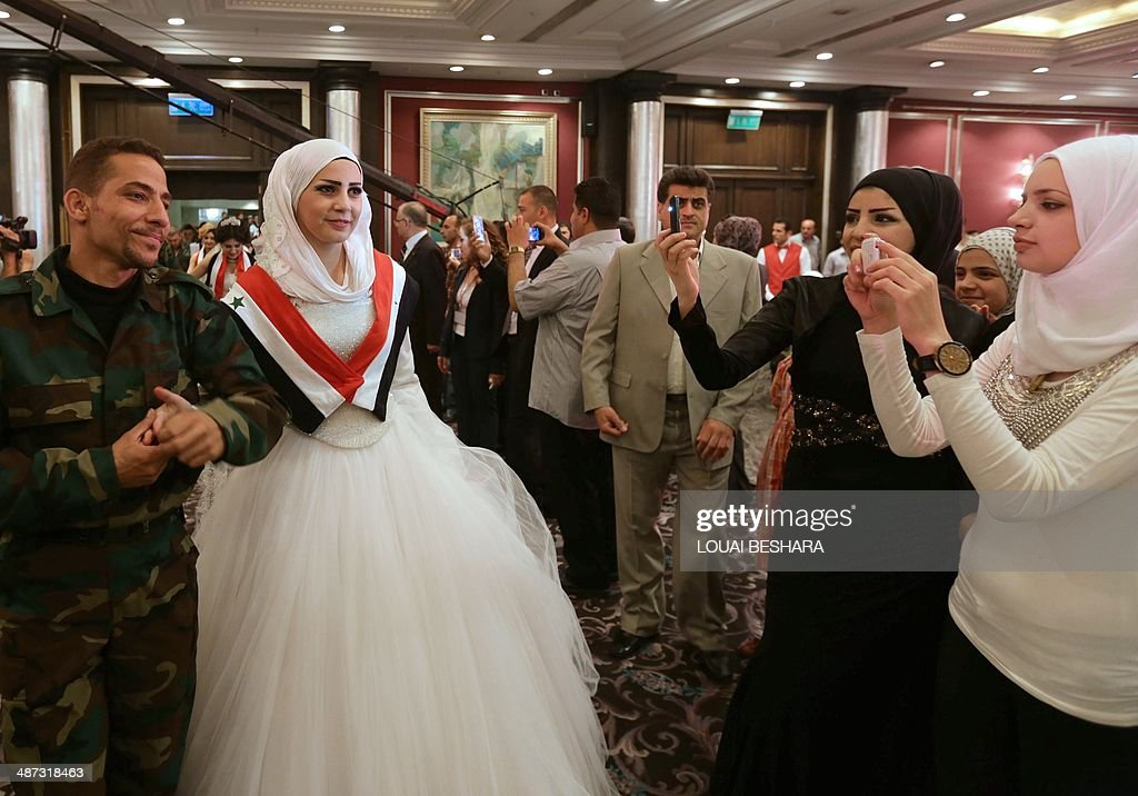 A Syrian couple pose for a photo during a group wedding ceremony made up of twenty government soldiers and their brides in Damascus on April 29, 2014.