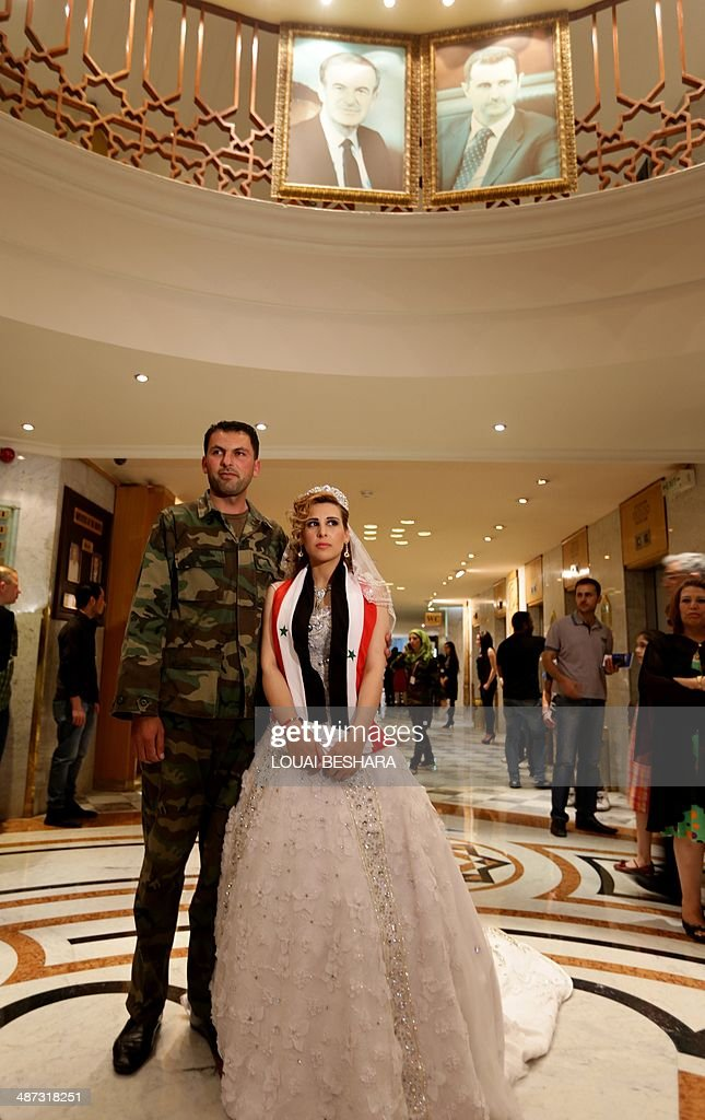 A Syrian couple pose for a photo under portraits of Syrian President Bashar al-Assad (top-R) and his father Hafez al-Assad during a group wedding ceremony made up of government soldiers and their brides in Damascus on April 29, 2014. AFP PHOTO/LOUAI BESHARA