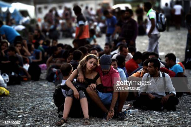 A Syrian couple waits with other migrants for the train near a train station at the FYR of Macedonia's village of Gevgelija on August 29 2015 The EU...