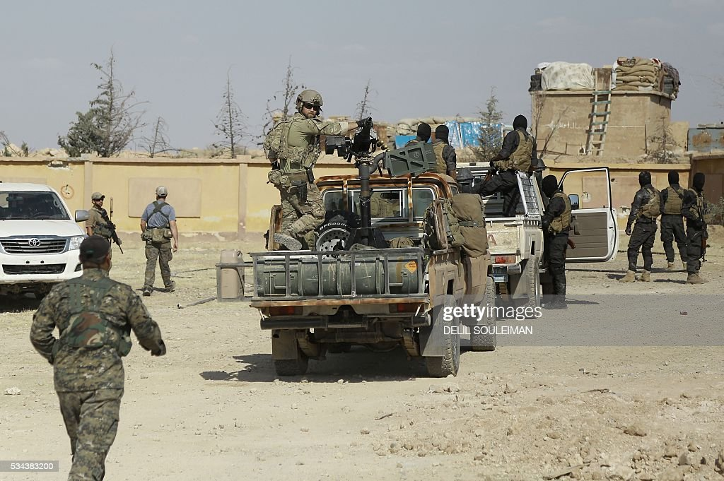 Syrian Democratic forces and an armed man in uniform identified by them as US special operations forces (C) are seen in the village of Fatisah in the northern Syrian province of Raqa on May 25, 2016. US-backed Syrian fighters and Iraqi forces pressed twin assaults against the Islamic State group, in two of the most important ground offensives yet against the jihadists. The Syrian Democratic Forces (SDF), formed in October 2015, announced on May 24 its push for IS territory north of Raqa city, which is around 90 kilometres (55 miles) south of the Syrian-Turkish border and home to an estimated 300,000 people. The SDF is dominated by the Kurdish People's Protection Units (YPG) -- largely considered the most effective independent anti-IS force on the ground in Syria -- but it also includes Arab Muslim and Christian fighters. SOULEIMAN