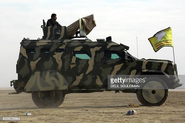 Syrian Democratic Forces driving a military vehicle supplied by the USled coalition advance in an area northeast of Raqa on February 5 during their...