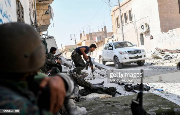 TOPSHOT Syrian Democratic Forces take position following a sniper shot in their direction on the eastern frontline of Raqa on September 24 2017...