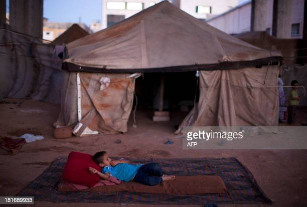 Syrian displaced child lies on a matress in an abandoned factory in the Sheikh Najjar industrial zone near Syria's northern city of Aleppo on...