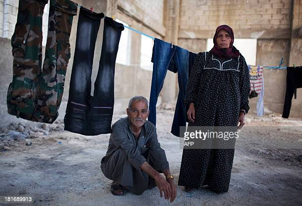 Syrian displaced Musa Mamoud and his wife Umm Yasin stand inside an abandoned factory in the Sheikh Najjar industrial zone near Syria's northern city...