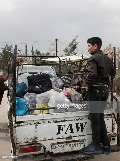 Syrian displaced residents of the besieged rebelheld town of Moadamiyet alSham in the suburbs of the capital Damascus wait at a checkpoint to return...