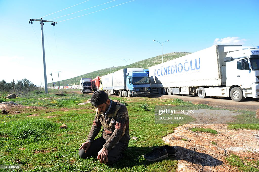 A Syrian driver prays near trucks queuing at the Cilvegozu border crossing between Turkey and Syria near Hatay on February 13, 2013 in the vicinity of the site where a vehicle exploded on February 11 in the buffer zone between Turkey and Syria. Fourteen people died in the blast.