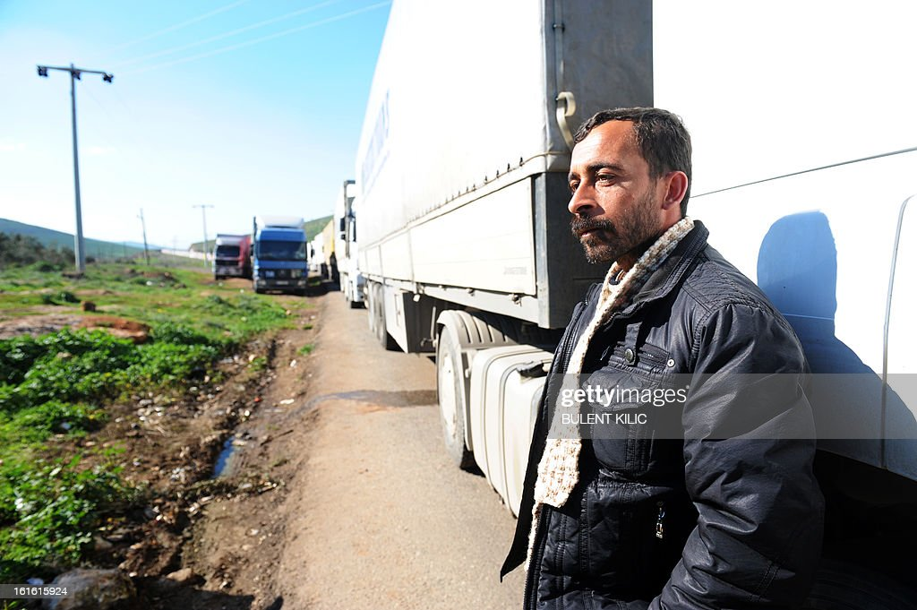 A Syrian driver stands by trucks queuing at the Cilvegozu border crossing between Turkey and Syria near Hatay on February 13, 2013 in the vicinity of the site where a vehicle exploded on February 11 in the buffer zone between Turkey and Syria. Fourteen people died in the blast.