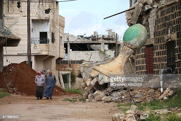 TOPSHOT Syrian elderly men walk past a damaged mosque in a rebelheld area of Daraa in southern Syria on March 28 2016 / AFP / MOHAMAD ABAZEED