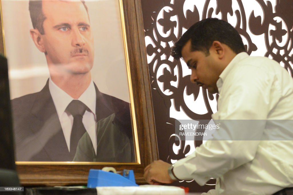 A Syrian embassy employee prepares a portrait of Syrian President Bashar al-Assad ahead of a press conference by Bouthaina Shaaban, a cabinet-level adviser to the Syrian president, at the India Islamic Centre in New Delhi on March 8, 2013. A top Syrian regime official thanked the BRICS group of emerging powers March 8 for its support, which she said had prevented Western military intervention and the 'destruction' of the country.