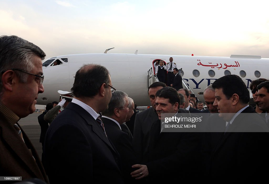 Syrian embassy officials greet Syrian Prime Minister Wael al-Halaqi (C) at Tehran's Mehrabad airport on January 15, 2013, a week after Syrian rebels freed 48 Iranians held hostage for more than five months. AFP PHOTO/BEHROUZ MEHRI