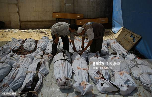 Syrian emergency personnel and a civilian inspect the bodies of Syrian men wrapped in plastic bags outside a makeshift hospital in the rebelheld area...