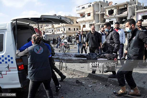 Syrian emergency services workers carry away a charred body on a stretcher following a double car bomb attack in the AlZahraa neighborhood of the...